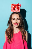 Muchacha bonita alegre que sostiene la caja de regalo en su cabeza Imagenes de archivo