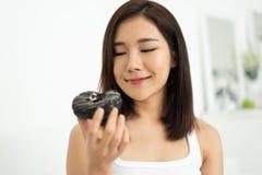 Muchacha bonita asiática que come el buñuelo del chocolate Fotografía de archivo