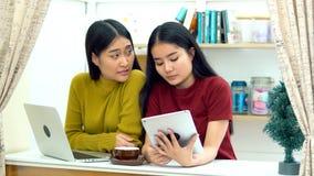 Muchacha bonita asiática que habla y que juega la tableta Foto de archivo libre de regalías