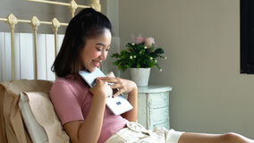 Muchacha bonita asiática que usa la tableta en el dormitorio Fotografía de archivo