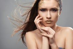 Muchacha bonita con arte de oro del maquillaje Imagenes de archivo