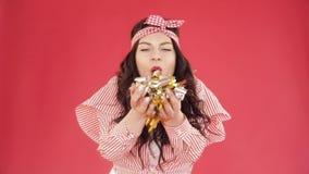 Muchacha bonita con confeti que sopla de la venda en la cámara metrajes