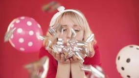 Muchacha bonita con confeti que sopla de la venda en la c?mara almacen de metraje de vídeo