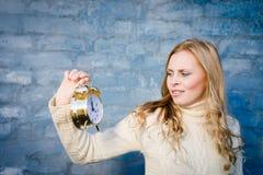 Muchacha bonita con el despertador de oro Imagenes de archivo