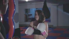 Muchacha bonita con el instructor que ejercita kickboxing en gimnasio en 4K almacen de metraje de vídeo