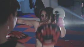 Muchacha bonita con el instructor que ejercita kickboxing en gimnasio en 4K metrajes