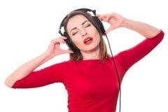 Muchacha bonita con el lápiz labial rojo y la ropa roja que escucha el m Fotos de archivo libres de regalías