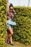 Muchacha bonita con el monopatín delante de la cerca verde Foto de archivo