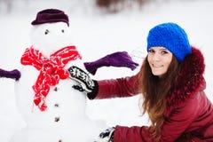 Muchacha bonita con el muñeco de nieve Fotografía de archivo