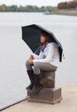 Muchacha bonita con el paraguas que se sienta en el muelle Fotos de archivo