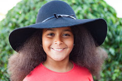 Muchacha bonita con el pelo afro largo y el sombrero negro Foto de archivo libre de regalías