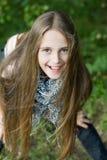 Muchacha bonita con el pelo largo en el parque del verde del verano. Fotografía de archivo