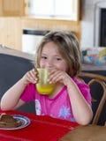 Muchacha bonita con el pelo levemente despeinado que se sienta en la mesa de desayuno Imagenes de archivo