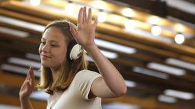 Muchacha bonita con el pelo rubio que escucha la música con los auriculares y el baile almacen de metraje de vídeo