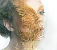 Muchacha bonita con el primer de la pluma del oro Foto de archivo libre de regalías