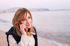 Muchacha bonita con el teléfono en la playa Foto de archivo