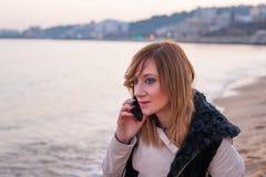 Muchacha bonita con el teléfono en la playa Fotos de archivo