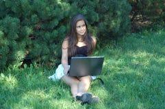 Muchacha bonita con la computadora portátil Fotos de archivo