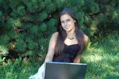 Muchacha bonita con la computadora portátil fotografía de archivo