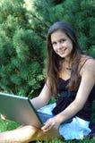 Muchacha bonita con la computadora portátil Imagenes de archivo