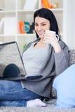 Muchacha bonita con la computadora portátil en el país que sonríe Fotografía de archivo
