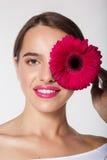 Muchacha bonita con la piel perfecta que sostiene la flor del gerbera Foto de archivo libre de regalías