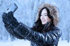 Muchacha bonita con la ropa del invierno que toma la foto Imágenes de archivo libres de regalías
