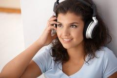 Muchacha bonita con la sonrisa de los auriculares Fotografía de archivo libre de regalías
