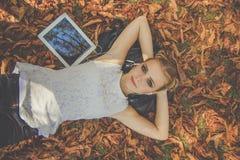 Muchacha bonita con la tableta digital en parque del otoño Imagen de archivo
