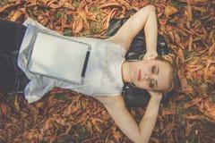 Muchacha bonita con la tableta digital en parque del otoño Foto de archivo libre de regalías