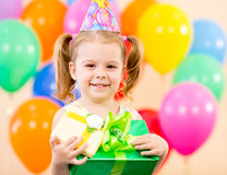 Muchacha bonita con los globos y el regalo coloridos Foto de archivo libre de regalías