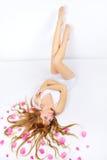 Muchacha bonita con los pétalos color de rosa en su pelo Fotos de archivo