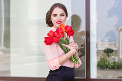 Muchacha bonita con los tulipanes rojos Imagen de archivo libre de regalías