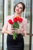 Muchacha bonita con los tulipanes y el teléfono rojos en manos Imagen de archivo