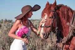 Muchacha bonita con los wildflowers en el carro del caballo en día de verano Fotos de archivo libres de regalías