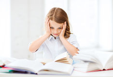 Muchacha bonita con muchos libros en la escuela Imagen de archivo libre de regalías