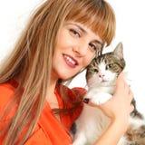 Muchacha bonita con un gato en un fondo blanco. Fotografía de archivo libre de regalías