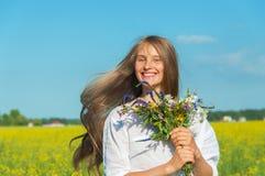 Muchacha bonita con un ramo en el campo Imagen de archivo libre de regalías