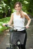 Muchacha bonita con una bicicleta imagenes de archivo