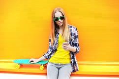 Muchacha bonita de la moda con el monopatín usando smartphone Fotos de archivo libres de regalías