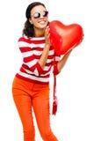Muchacha bonita de la raza mixta que sostiene el globo rojo del corazón Fotografía de archivo