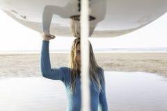 Muchacha bonita de la resaca con un longboard en la playa imagenes de archivo