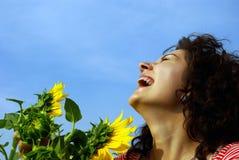 Muchacha bonita de risa con un girasol Fotografía de archivo