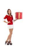 Muchacha bonita de santa que sostiene el regalo Fotografía de archivo