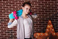 Muchacha bonita del adolescente con el monopatín azul Fotos de archivo