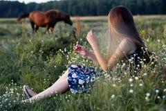 Muchacha bonita del adolescente con el pelo largo sano que se sienta en el prado en día de verano fotografía de archivo libre de regalías