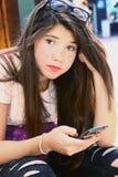 Muchacha bonita del adolescente con el pelo marrón largo que charla en cierre del smartphone encima del retrato Fotografía de archivo libre de regalías