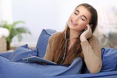 Muchacha bonita del adolescente con la sentada de la tableta Imagen de archivo libre de regalías