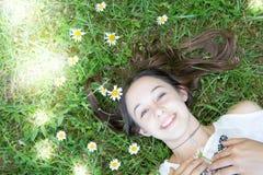 muchacha bonita del adolescente en un prado con las flores y el sol Imagenes de archivo