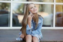 Muchacha bonita del adolescente que se sienta al aire libre y que habla por el teléfono Foto de archivo libre de regalías